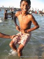 a kid in kanyakumari beach tries to fix towel on his waist