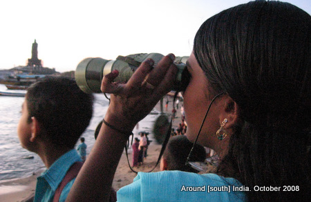 a lady uses binoculars to watch the sunrise in kanyakumari