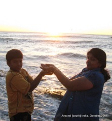 a mother and her son try to bring the rising sun on their palms