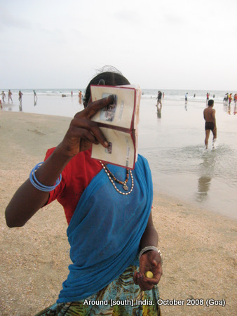 a woman painter at kolva beach hides her face from camera