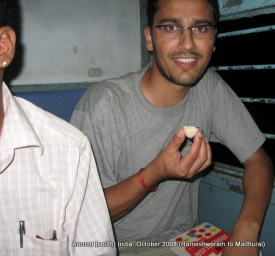 dinesh wagle eating laddu that his co-passengers offered to him
