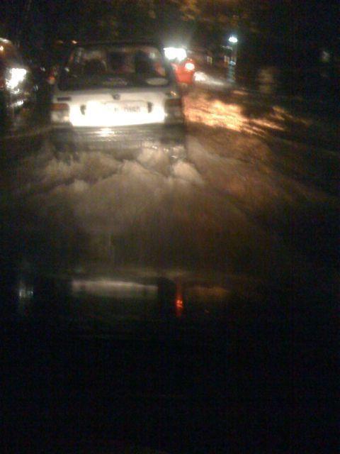 a car sails through waterlogged delhi road
