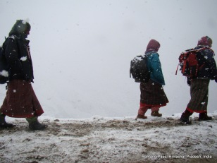women walking under snow at rohtang pass, india