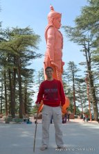 standing alongside hanuman holding a stick to put monkeys at bay