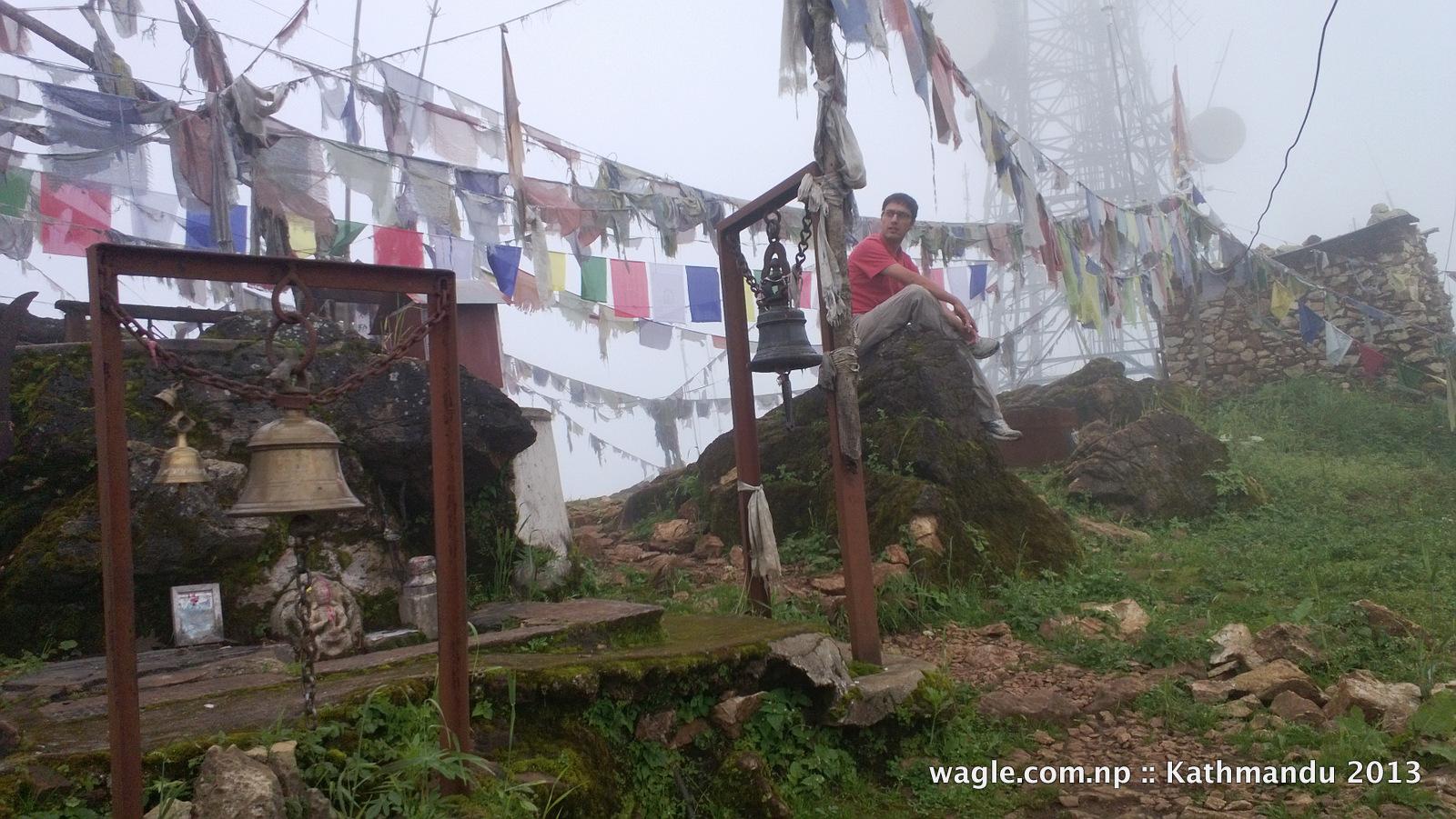 Dinesh Wagle at Phulchowki. Bells, prayer flags and trishuls