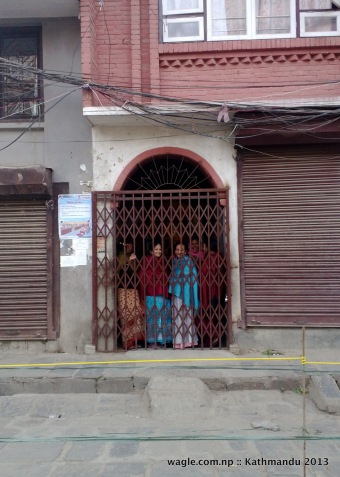 residents of a house in kathmandu-7 constituency that had a polling station at its courtyard peek from inside as the iron gate was locked by the police