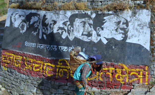 A woman walks past a Maoist mural at the entrance of Thabang village, Rolpa: 1st line: Workers of the world, unite. 2nd line: No election campaign zone!