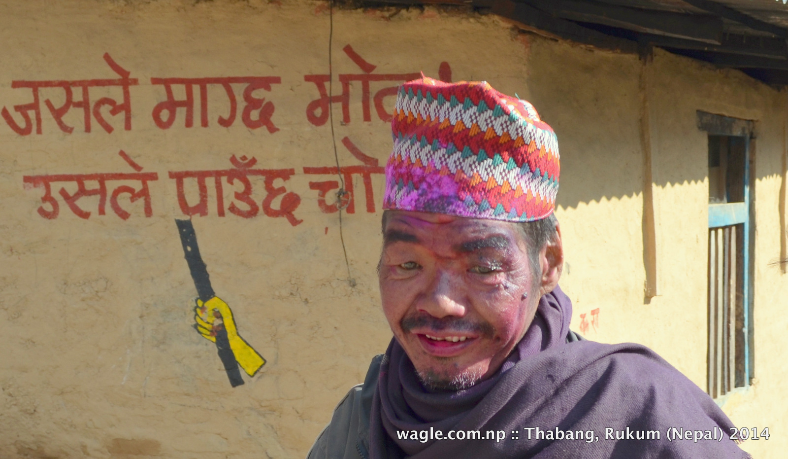 A man in Thabang, Rolpa, face smeared with colored powder, celebrated Maghi festival. On the background is an anti-election slogan-