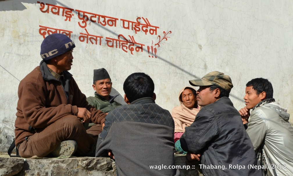 In a recent sunny afternoon the people of Thabang, Rolpa gathered to chat under a Maoist anti-election graffiti. 1st line: Don't divide Thabang; 2nd line: Middlemen leaders are not needed.