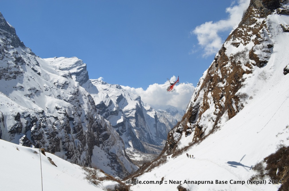 A helicopter flew over the trekkers who were approaching the Machhapuchhere Base Camp via the tril in the Modi Khola river valley-- as seen from Machhapuchhre Base Camp, with snowcapped Mardi Himal on the left