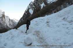 A trekker walked on the snow-covered trail in the Modi Khola river valley near Machhapuchhre Base Camp