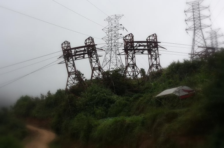 At a hilltop near Kathmandu city. The old ghiring cables, now defunct, go underneath the bijuli transmission lines. These towers separate Kathmandu from Makwanpur district.