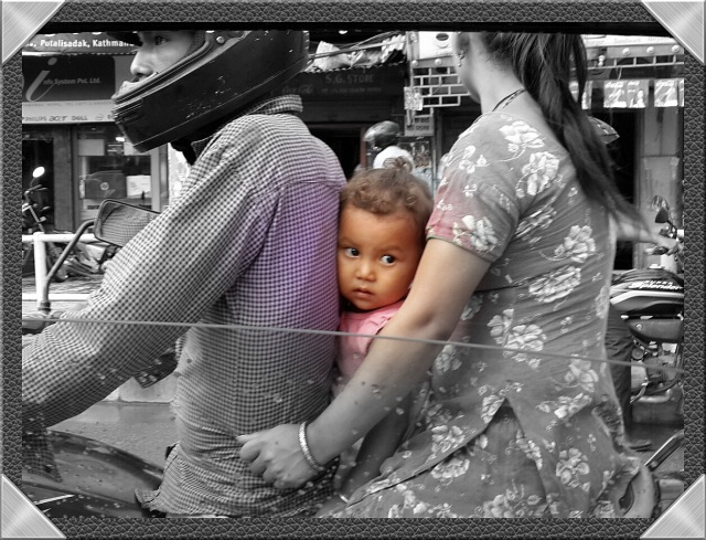 Tucked between her mama and papa. Kathmandu. Originally spotted by George Georgiou.