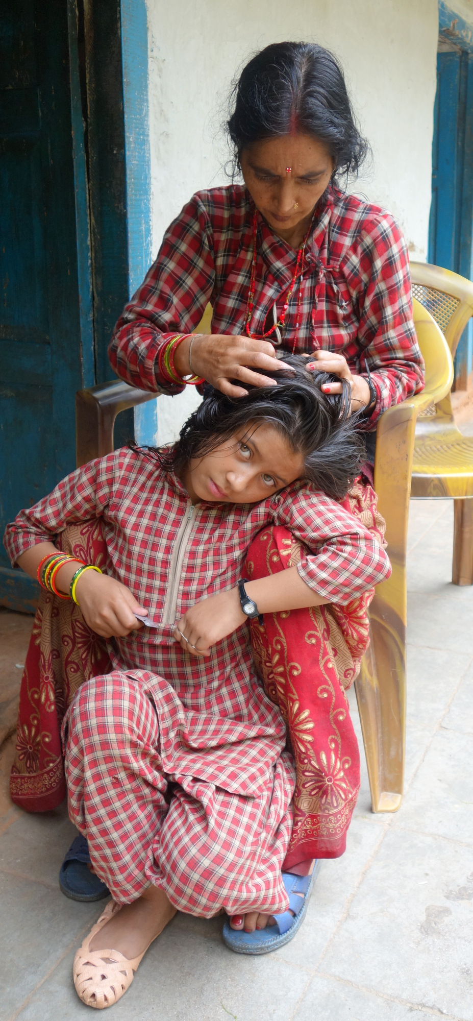 In Chandanpur village, a grandma looks for lice in her granddaughter's hair.