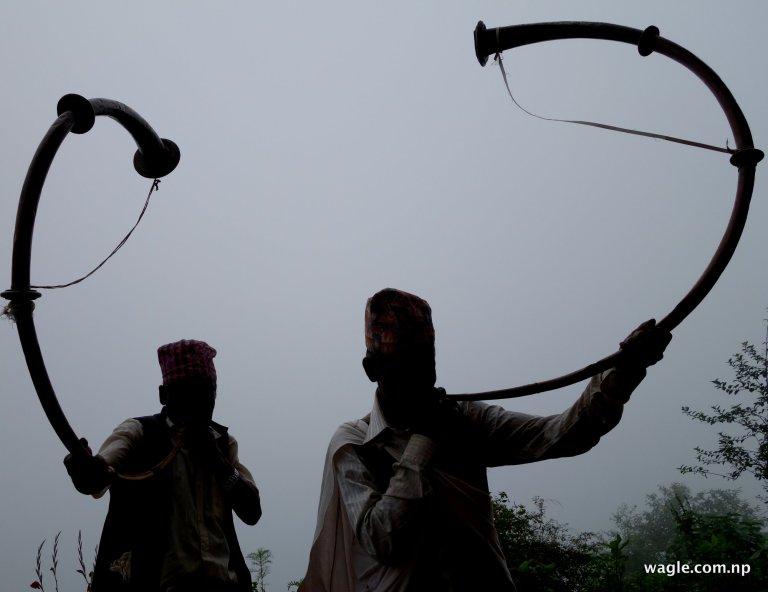 Two men blowing Narsinghas